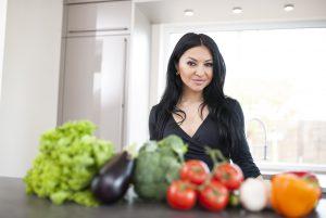 Fitness Model Oxana beim Kochen mit Gemüse, Fitnessernährung